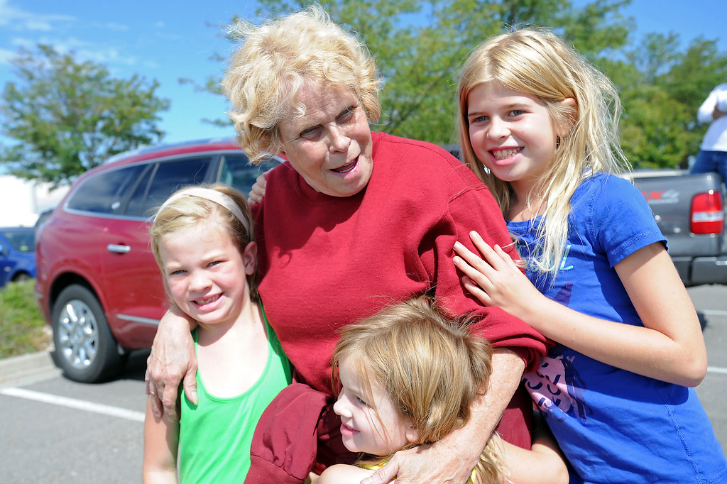 Description of . Drake resident Carolyn Dunning, middle, hugs her granddaughters, front from left, Meredith Beller, 7, Hadley Beller, 4, and Rachel Beller, 10, on Saturday, Sept. 14, 2013 at the Fort Collins/Loveland Municipal Airport where she was transported by helicopter after being stranded in Drake by recent flooding.  (Photo by Steve Stoner/Loveland Reporter-Herald)
