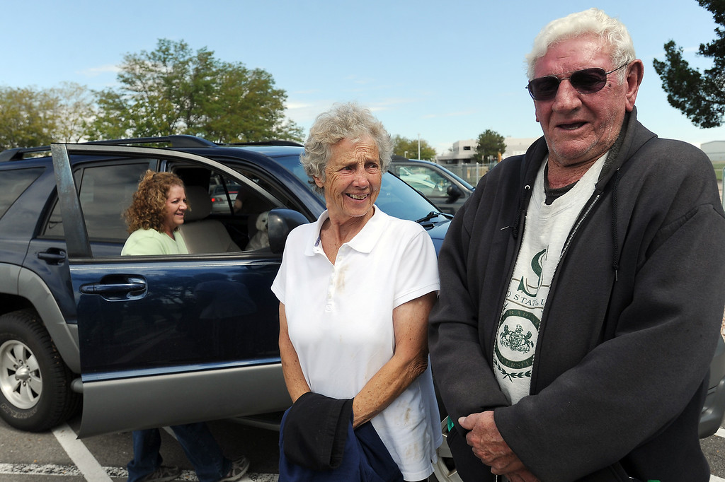. Leroy Rady, right, and his wife Marge Rady stand together at the Fort Collins/Loveland Municipal Airport where they were transported by a helicopter owned by Century Link after being stranded by flooding at their home in Drake. Their daughters Terri Rady, back left, and Sharon Rady, not pictured, picked them up at the airport. (Photo by Steve Stoner/Loveland Reporter-Herald)