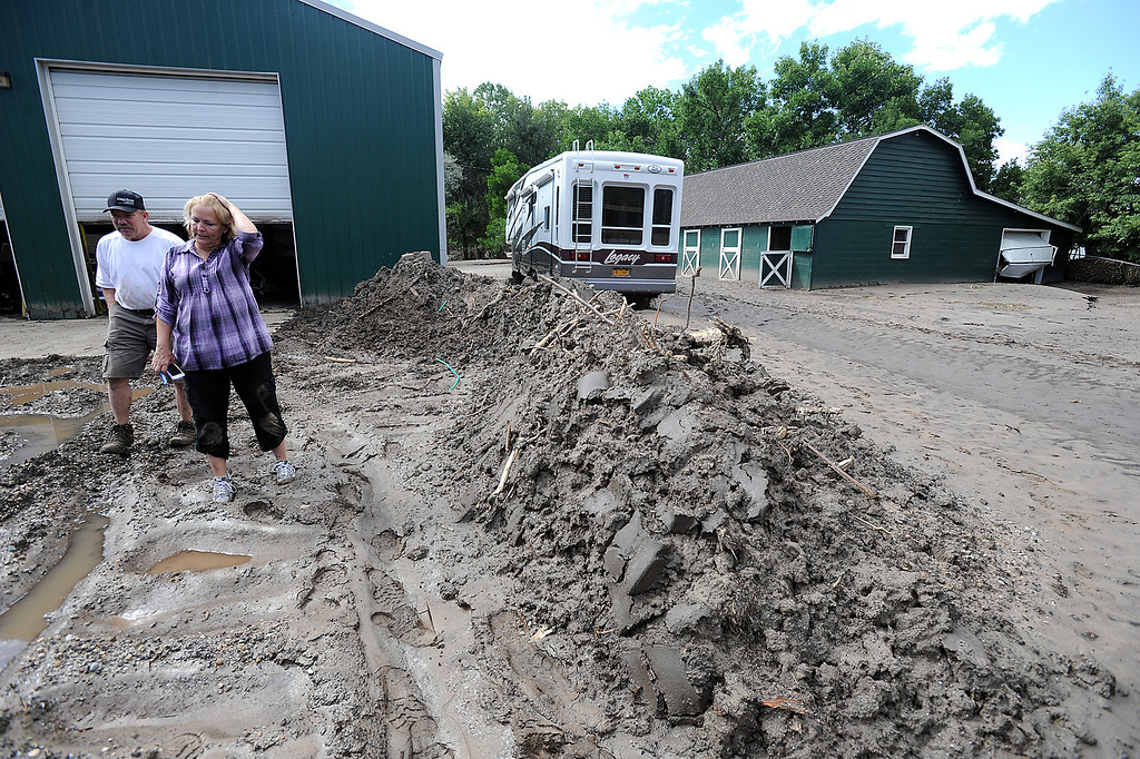 Description of . Diana Carnahan, right, and her husband Ken stand surrounded by mud left behind from the flood near their workshop and barn at their Glade Road home Monday, September 16, 2013. (Photo by Jenny Sparks/Loveland Reporter-Herald)