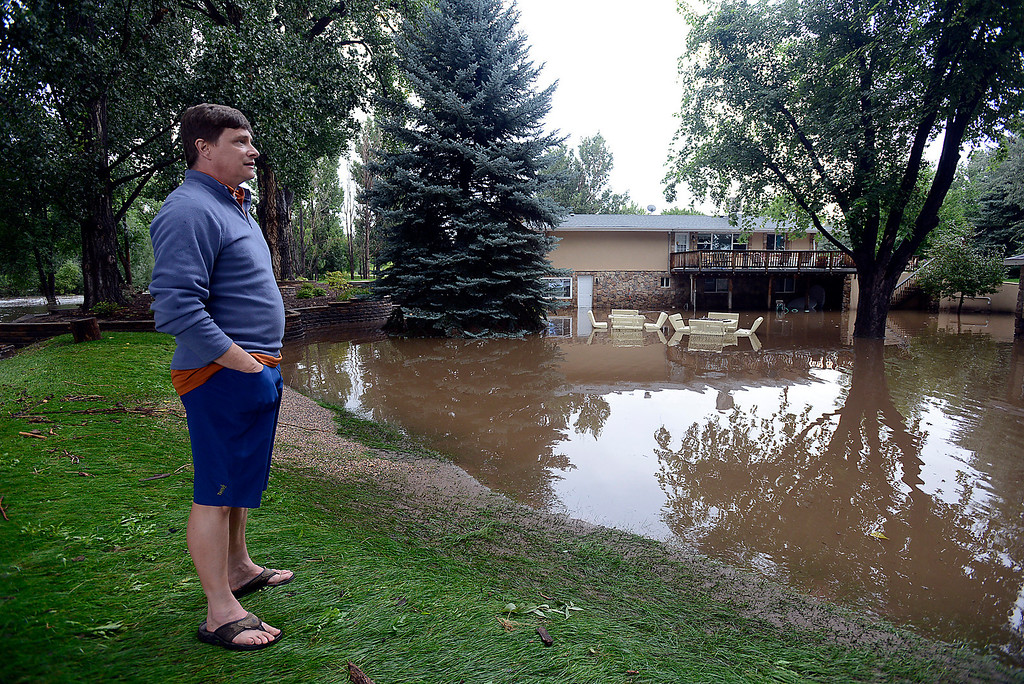 . Peter Williams looks at his neighbor\'s home, which is standing in flood waters from the Big Thompson River on the 6700 block of Glade Road on Sunday, September 15, 2013 west of Loveland. (Photo by Jenny Sparks/Loveland Reporter-Herald)
