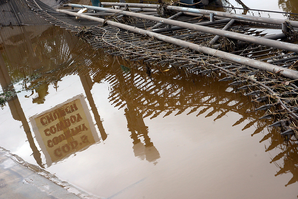 Description of . A destroyed wroght iron fence at God\'s Country Cowboy Church is reflected in flood water in west Loveland on Sunday, September 15, 2013 west of Loveland. (Photo by Jenny Sparks/Loveland Reporter-Herald)