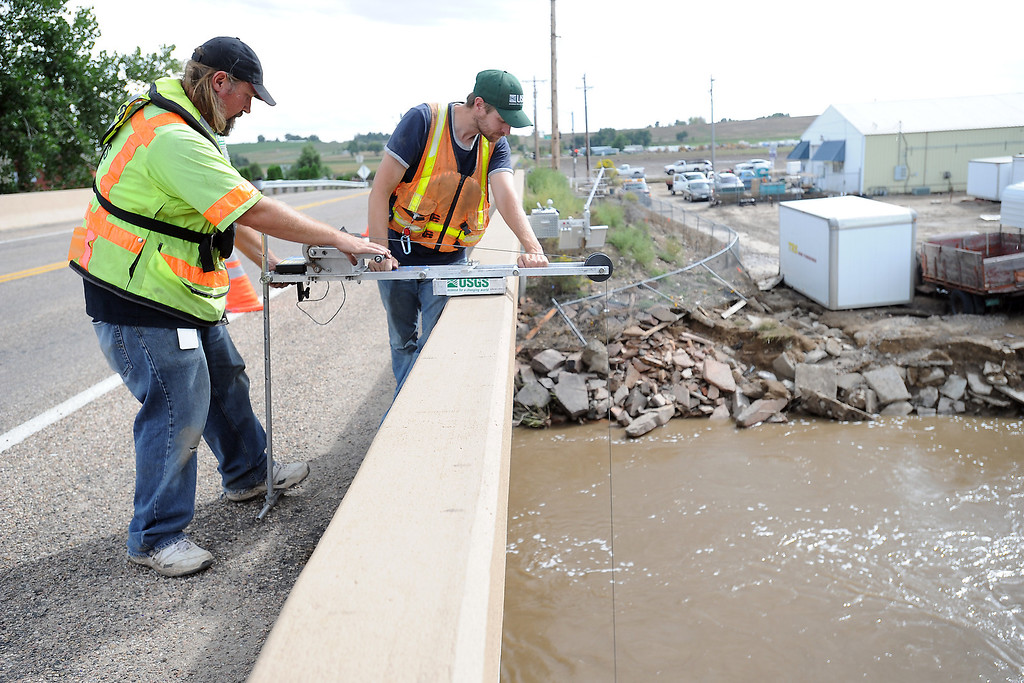 Description of . U.S. Geological Survey hydrologist Jeff Bails, left, and hydrologic technician Ben Glass lower a velocity meter into the Big Thompson River to measure water flow Wednesday, Sept. 18, 2013 from the St. Louis Avenue bridge just north of Highway 402 in southeast Loveland, Colo. The men also installed a rapid deployment gauge since the permanent stream gauge was damaged by recent flooding. (Photo by Steve Stoner/Loveland Reporter-Herald)