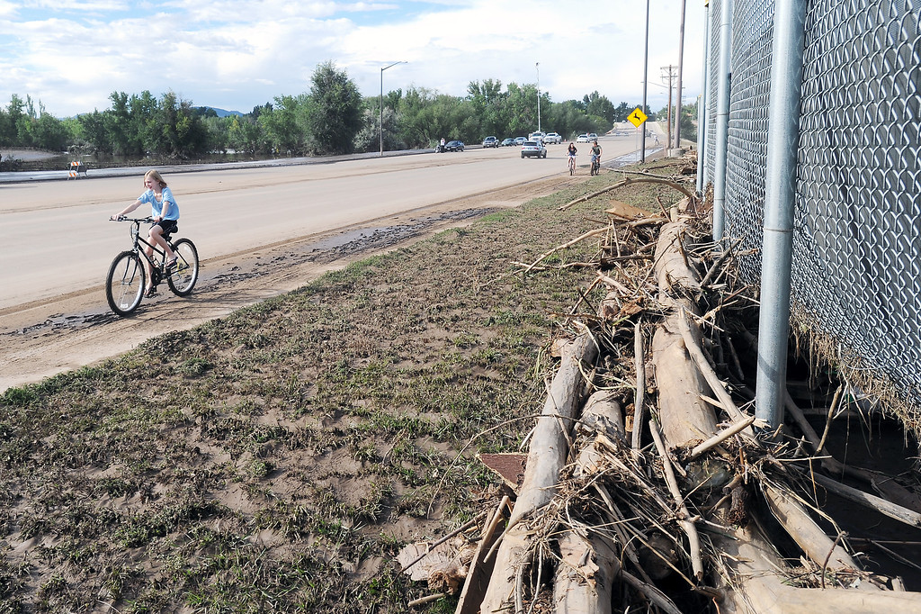 Description of . Haley Yarbrough, 11, rides her bike on the sidewalk on Taft Avenue just north of First Street where mud and debris from recent flooding has deposited along the Centennial Park baseball fields. (Photo by Steve Stoner/Loveland Reporter-Herald)