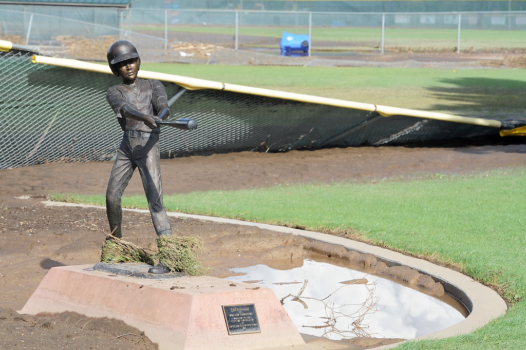 """Description of . Donald Thompson\'s sculpture \""""The Slugger\"""" at Centennial Park in Loveland, Colo., is covered with mud and vegetation Saturday, Sept. 14, 2014 after recent flooding in the area that also damaged several outfield fences at the park. (Photo by Steve Stoner/Loveland Reporter-Herald)"""