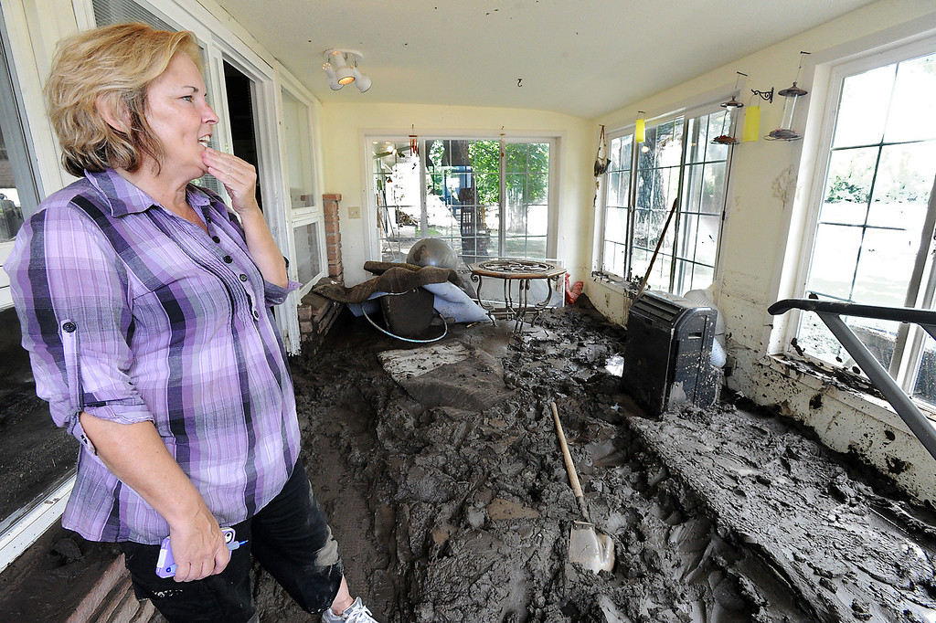 Description of . Diana Carnahan stands Monday, September 16, 2013 in her sunroom of her Glade Road home which is now filled with mud from the Big Thompson River flooding. (Photo by Jenny Sparks/Loveland Reporter-Herald)