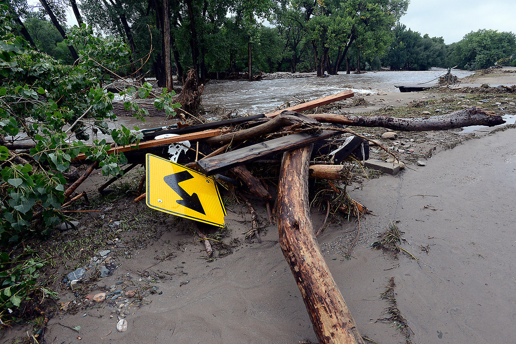 . A road sign is among the debris near the Big Thompson River off Glade Road on Sunday, September 15, 2013 west of Loveland. (Photo by Jenny Sparks/Loveland Reporter-Herald)