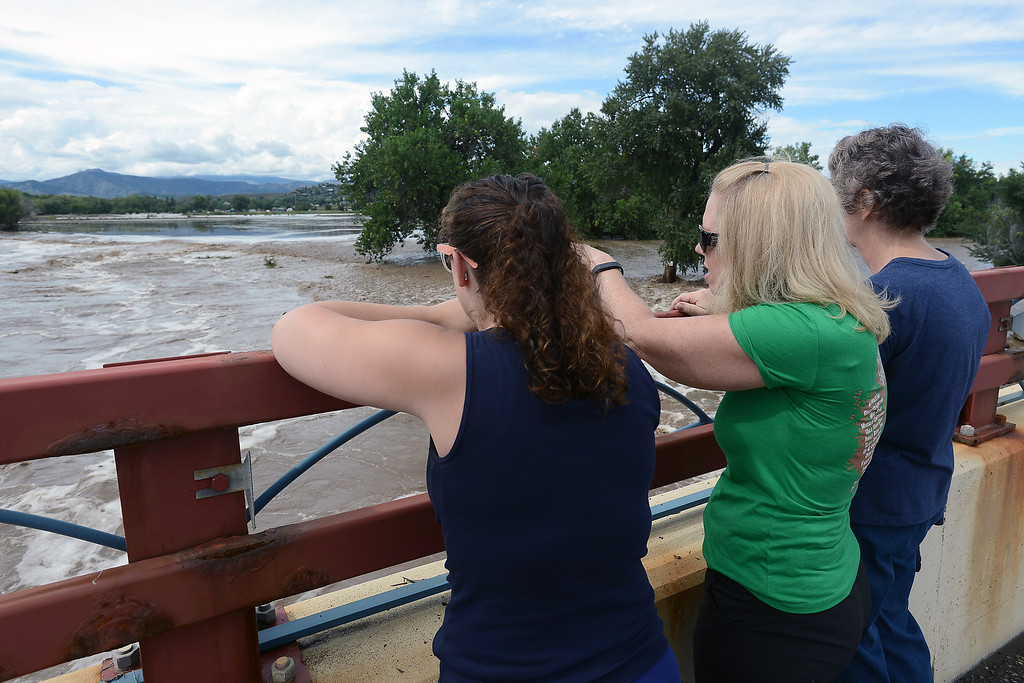 . Sarina Netzel, left, Nancy Netzel and Mary Stimps look out at the flooded Big Thompson River on Friday from the Wilson Avenue bridge Loveland, Colo. (Photo by Steve Stoner/Loveland Reporter-Herald)