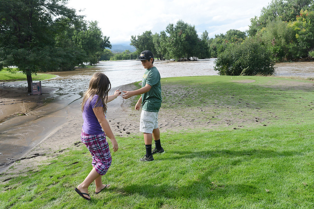 . Madi Jurarz, 12, left, hands a pebble to Adrian Juarez, 14, to throw into the Big Thompson River where the river\'s water flooded near hole No. 16 at Marianna Butte Golf Course in Loveland, Colo.  (Photo by Steve Stoner/Loveland Reporter-Herald)