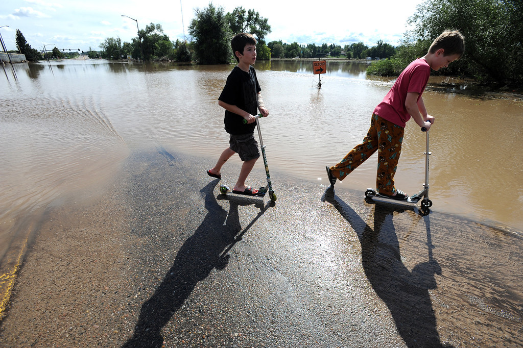 . Westley Byloo, 11, left, and pal Logan Beecher, 11, ride their scooters near the flood water covering Taft Avenue north of First Street on Friday, September 13, 2013. (Photo by Jenny Sparks/Loveland Reporter-Herald)