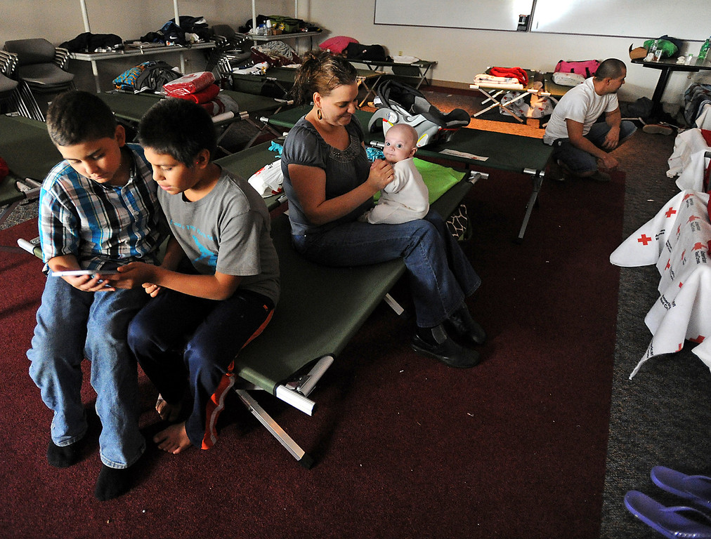 ". Flood evacuee Daisy Velasco plays with her baby Caleb Bernal, 4 months, as her nephew Joan Favela, 11, left, and Jesus Jimenez, 12, play a video game at the Red Cross Shelter in Loveland Friday, September 13, 2013. Velasco said ""Not being home\"" has been difficult. (Photo by Jenny Sparks/Loveland Reporter-Herald)"