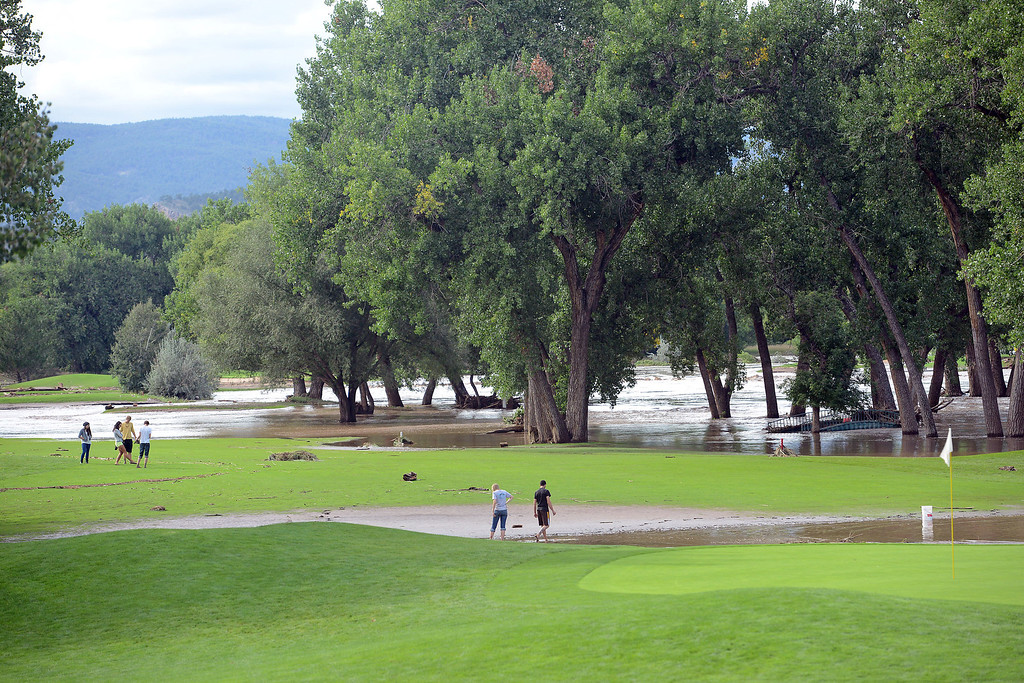 . Groups of people walk near the No. 17 green at Marianna Butte Golf Course on Friday where recent flooding has submerged parts of the course in water. (Photo by Steve Stoner/Loveland Reporter-Herald)