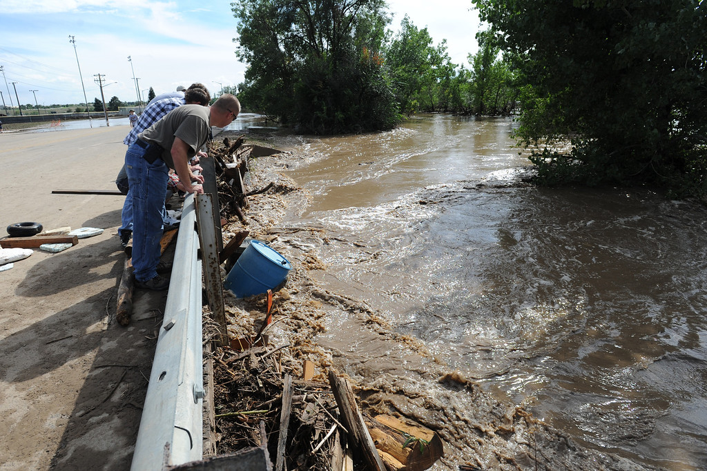 . Stephen Strack checks out the debris and high running water in the Big Thompson River on Taft Aveenue in Loveland on Friday, September 13, 2013. (Photo by Jenny Sparks/Loveland Reporter-Herald)