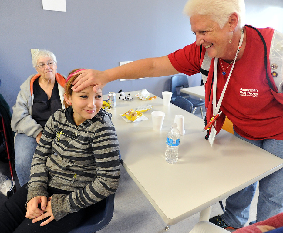. Pam Robinson, right, a registered nurse volunteer with the American Red Cross, checks on flood evacuee Julissa Garcia, 13, at the shelter in Loveland on Friday, September 13, 2013. Garcia was not feeling well. (Photo by Jenny Sparks/Loveland Reporter-Herald)