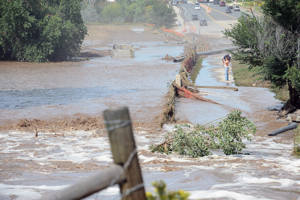 . Overflowing water from the Big Thompson River covers the Loveland Recreation Trail where it goes under the Wilson Avenue bridge in Loveland, Colorado. (Photo by Steve Stoner/Loveland Reporter-Herald)