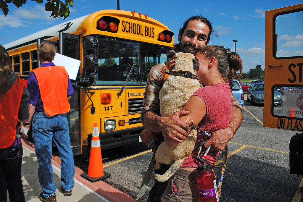 . Kalyn Taylor, right, hugs Alexander Diederich and their pug Phoebe after they arrived at Timberline Church in Fort Collins on Monday September 16, 2013. Diederich was one of the evacuees rescued from Drake along with Phoebe his dog. (Photo by Lilia Munoz/Loveland Reporter-herald)