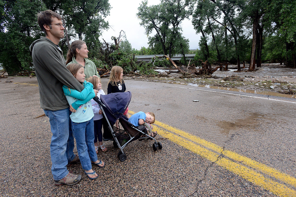 . The Bounds family looks at the destruction from flooding at Glade Park on the Big Thompson River west of Loveland on Sunday, September 15, 2013 west of Loveland. (Photo by Jenny Sparks/Loveland Reporter-Herald)