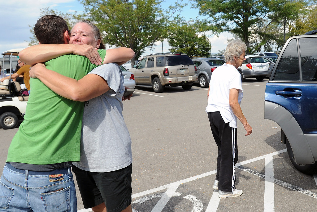 . Robert Egloff, left, hugs Sharon Rady on Saturday, Sept. 14, 2013 at the Fort Collins/Loveland Municipal Airport where Sharon was picking up her mother Marge Rady, back, and father, not pictured, who were flown out of Drake where they were stranded by recent flooding.  (Photo by Steve Stoner/Loveland Reporter-Herald)