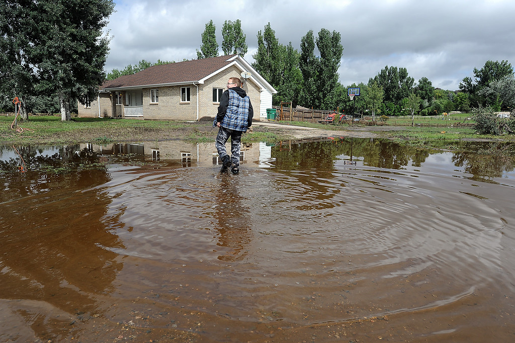 . Austin Johnson, 12, walks Monday, September 16, 2013, across standing water on his street to get to his house to feed his dogs and cat off Glade Road. His family was evacuated after the flood. (Photo by Jenny Sparks/Loveland Reporter-Herald)