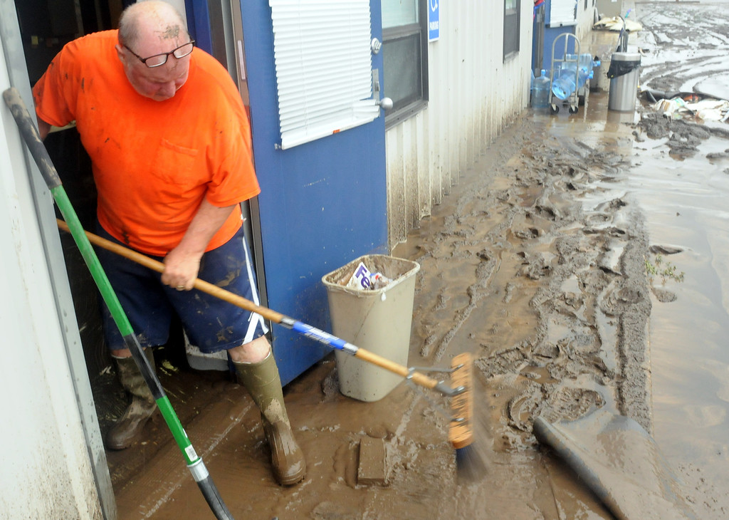 . Dan Davidson, owner of Enterprise Technologies Inc., pushes mud out of his business at 418 E. Eighth St. on Sunday afternoon, Sept. 15, 2013. The nearby Big Thompson River filled Davidson\'s offices with 18 inches of water and left behind 2-3 inches of mud. (Photo by Craig Young)