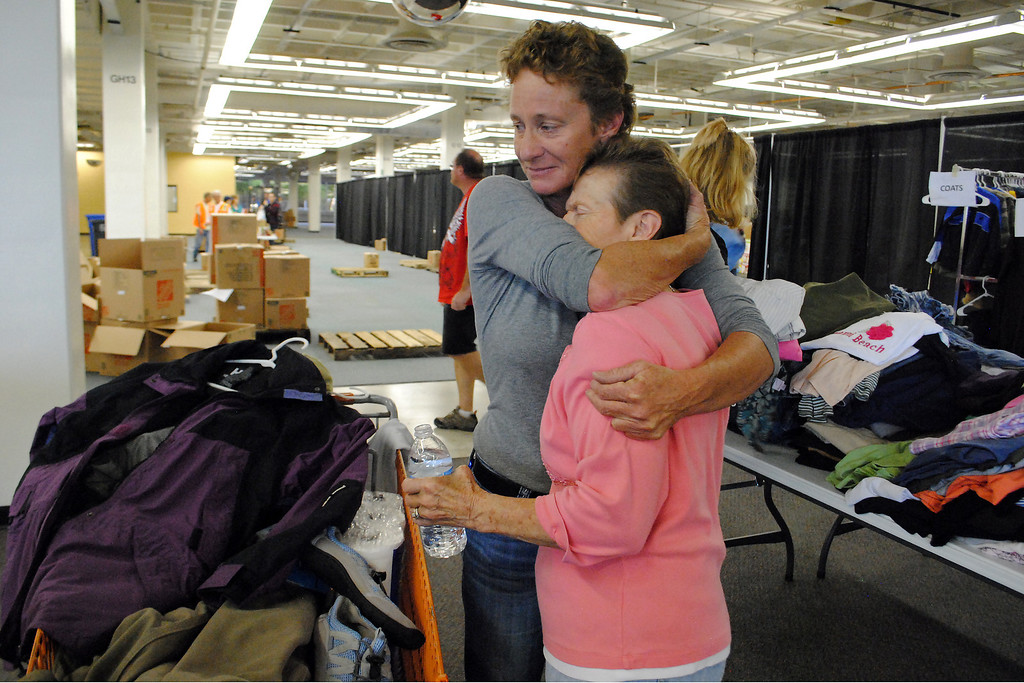 . Tina Anderson, left, comforts her mom Barb Anderson, while they get coats and other essentials at the Donation Center in the Former Agilent Campus Building in Loveland on Monday September 16, 2013. Barb and her husband Andy where evacuated from their home a couple miles up from the Dam Store. (Photo by Lilia Munoz/ Loveland Reporter-Herald)