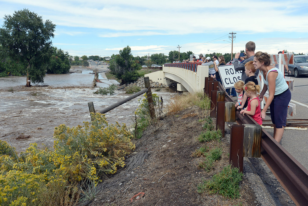 . Erin Greiss, right, Lucy Greiss, 6, Owen Greiss, 8, Maddie Greiss, 4, and Luke Greiss join others watching the flooding Big Thompson River on Friday from the bridge across Wilson Avenue in Loveland, Colo. (Photo by Steve Stoner/Loveland Reporter-Herald)