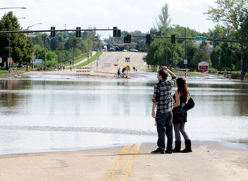 . Adam Small and Natalie Weingardt look across Taft Avenue which is flooded north of First Street in Loveland on Friday, September 13, 2013. (Photo by Jenny Sparks/Loveland Reporter-Herald)