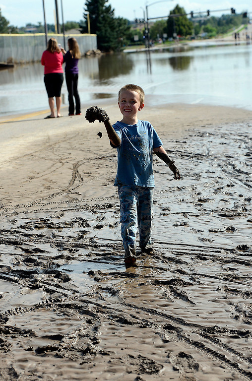. Quinn Doyle, 5, plays in the mud from the flood waters on Taft Avenue in Loveland on Friday, September 13, 2013. (Photo by Jenny Sparks/Loveland Reporter-Herald)